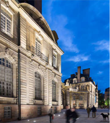 People noticing the architecture lighting in front of a building at Grand Île, Strasbourg lit by Philips lighting