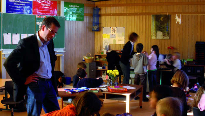 A teacher helps students at In der Alten Forst, illuminated by Philips school lighting