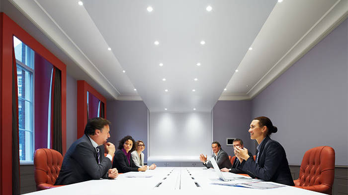 People attending a meeting under Philips meeting room lighting