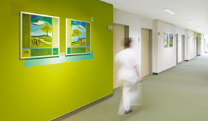 Nurse is walking in a green hospital's corridor