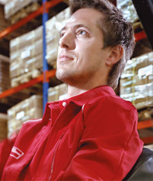 Male worker operates a forklift in a sustainable warehouse. - retail lighting