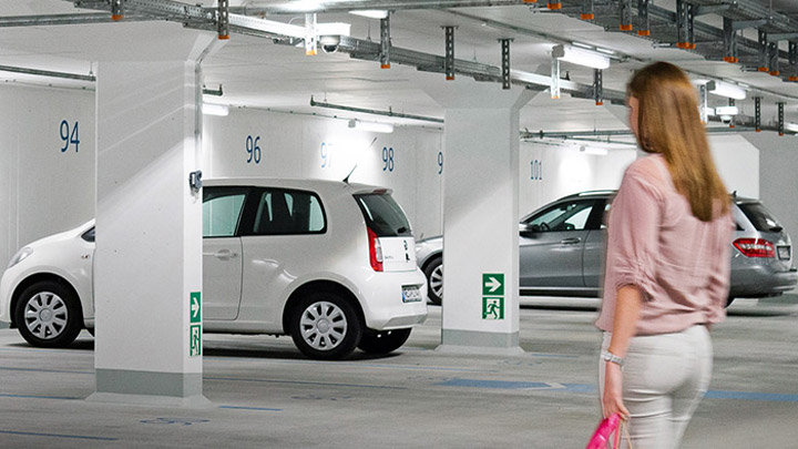 Woman walks to car in well-lit underground car park